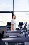 Muscular man running on a treadmill in a fitness club Stock Photos