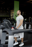 Muscular man running on a treadmill in a fitness club Stock Photography