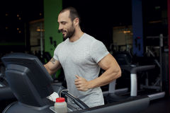 Muscular man running on a treadmill in a fitness club Royalty Free Stock Images