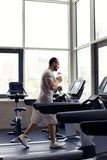 Muscular man running on a treadmill in a fitness club Stock Image