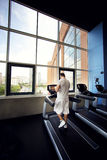 Muscular man running on a treadmill in a fitness club Royalty Free Stock Photography