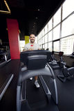 Muscular man running on a treadmill in a fitness club Stock Photo
