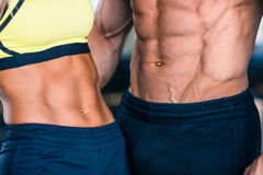 Muscular man's and sporty woman's torso Royalty Free Stock Image