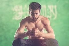 Muscular man with Saudi Arabia Flag behind Royalty Free Stock Photos