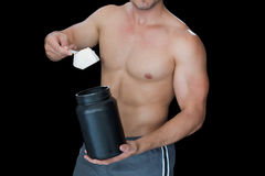 Muscular man scooping up protein powder Stock Image