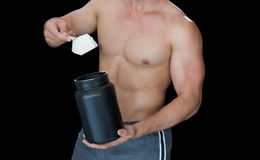 Muscular man scooping up protein powder Royalty Free Stock Photos