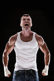 Muscular man screaming and roar. Black background stock photography