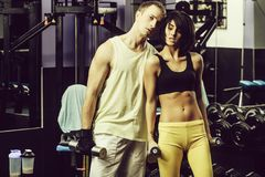 Muscular man and girl at gym trainer with dumbbells. Couple of pretty women or cute girl with belly and handsome men with muscular body training in sport gym at stock photo