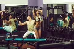 Muscular man and girl at gym trainer with dumbbells. Happy smiling couple of pretty women or cute girl with belly and handsome men with muscular body training in royalty free stock images