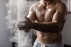 Muscular man shaking chalk off his hands Stock Photo