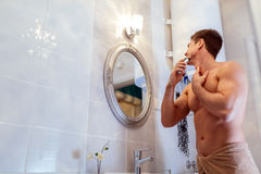 Muscular man shaving in bathroom. With towel wrapped around waist Royalty Free Stock Photos