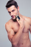 Muscular man shaving with electric razor Royalty Free Stock Photos