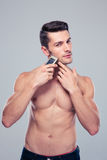 Muscular man shaving with electric razor Stock Images