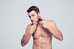 Muscular man shaving with electric razor Stock Image