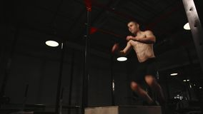 Muscular man without a shirt performs vertical jumps on a wooden box. Aerobic exercise. Muscular man without a shirt performs vertical jumps on a wooden box stock video