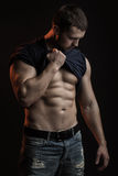 Muscular man with shirt on shoulder. One handsome sexual strong young man with muscular body in blue jeans with shirt on shoulder standing posing in studio on Stock Image