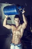 Muscular man shirtless, carrying gas tank over head Royalty Free Stock Images