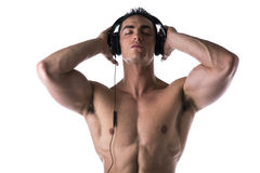 Muscular man shirtless, listening to music on headphones Stock Images