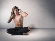 Muscular man shirtless listening to music on headphones Stock Photo
