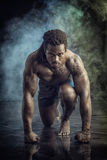 Muscular man shirtless, ready to sprint and run. Handsome young muscular black man shirtless ready to sprint and run. On dark background with smoke royalty free stock photo