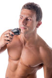 Muscular man shirtless using electric shaver, looking away Royalty Free Stock Photography