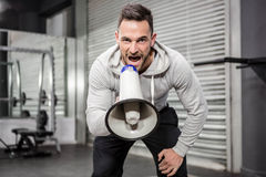 Muscular man shouting on megaphone. At the crossfit gym Stock Photo