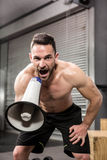 Muscular man shouting on megaphone. At the crossfit gym Royalty Free Stock Image