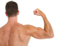 Muscular man showing biceps. Rear view Stock Photo