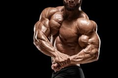 Muscular man showing muscles and biceps  on the black background. Bodybuilder male naked torso abs royalty free stock photos