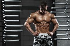 Muscular man showing muscles, posing in gym. Strong male naked torso abs, working out.  royalty free stock image