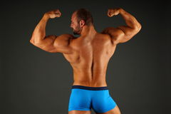 Muscular man shows his back Stock Photo