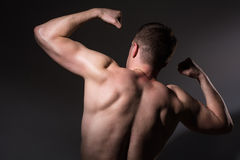 Muscular man shows his biceps back. Athletic man on a dark background Stock Image