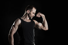 Muscular man,  shows his biceps, black background, place for text on the right Royalty Free Stock Photos