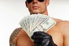 Muscular man shows money Royalty Free Stock Image