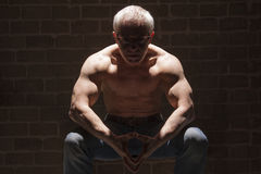 Muscular man sitting in spotlight Stock Image