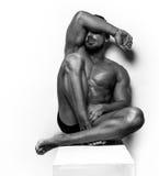 Muscular Man sitting on white Royalty Free Stock Photos