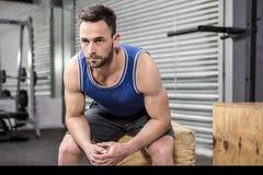 Muscular man sitting on wooden block Stock Photo