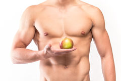 Muscular man with six-pack holding apple Royalty Free Stock Photos