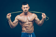 Muscular man skipping rope. Portrait of muscular Royalty Free Stock Image