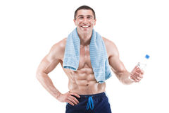 Muscular man smiling with blue towel over neck, drinking water, isolated on white background. Young muscular man smiling with blue towel over neck, drinking Royalty Free Stock Photography
