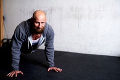 Muscular man smiling at camera while doing pushup Royalty Free Stock Photography