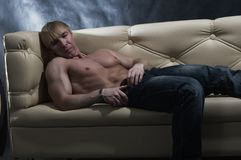 Muscular man on sofa Royalty Free Stock Photography