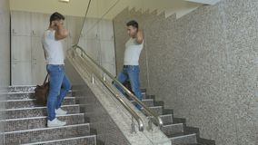 Muscular man with sportive bag moves up stairs. Muscular guy moves up on the stairs in the sport center. Handsome man holds a sportive bag in hand. Sportsman stock video
