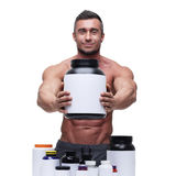 Muscular man with sports nutrtion Royalty Free Stock Photography