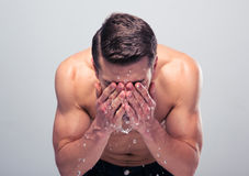 Muscular man spraying water on his face Royalty Free Stock Photography
