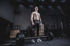 Muscular man Standing at Barbells Before Exercise. stock images