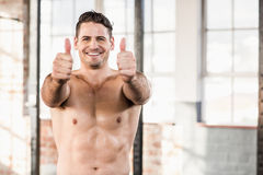 Muscular man standing in front of the camera with his thumbs up Stock Images