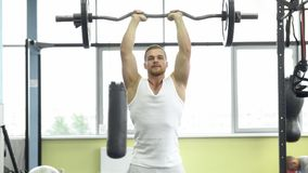 Muscular man on strength training in the gym. Athlete makes triceps exercise with a barbell royalty free stock photography