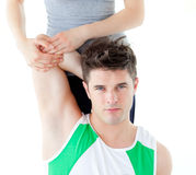 Muscular man stretching with female coach Stock Images