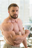 Muscular man. Strong muscular man looking straight at the camera. Bodybuilder with huge muscles stock photo